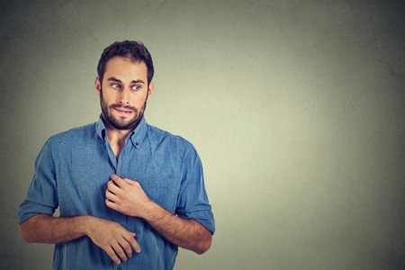 awkward: Portrait young man opening shirt to vent, its hot, unpleasant, awkward situation, playing nervously with hands. Embarrassment. Isolated gray background. Negative emotions facial expression feeling Stock Photo