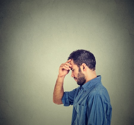 the thoughtful: Side profile young thoughtful man isolated on gray wall background with copy space