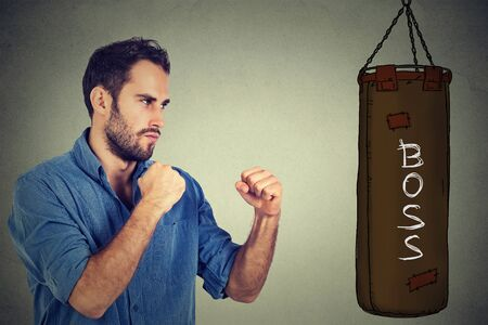 anger management: man ready to punch boxing bag with word boss written on it. negative emotion feelings. Employee employer relationship concept Stock Photo