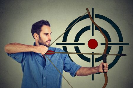 hit man: Side profile man trying to hit a target with bow and arrow Stock Photo
