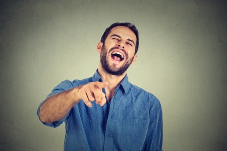 Laughing young guy pointing with finger at camera