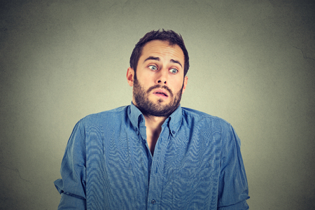men shirt: Closeup portrait young handsome man shrugging shoulders who cares so what I dont know gesture isolated on grey wall background. Body language expression. Man showing ignorance