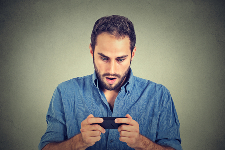 portrait Gros plan anxieux jeune homme regardant téléphone voir de mauvaises nouvelles ou des photos avec émotion peur sur son visage isolé sur gris fond mur. L'émotion humaine, la réaction, l'expression Banque d'images