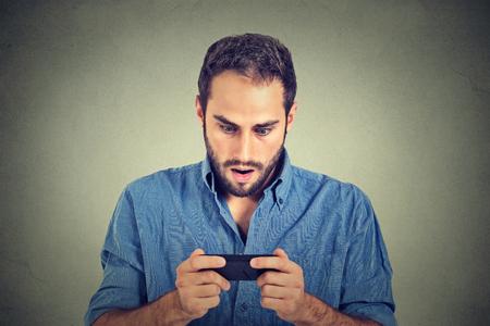sorprendido: Retrato del primer joven ansiosa que mira el teléfono de observación de malas noticias o fotos con la emoción de miedo en su cara aislada en el fondo de la pared gris. La emoción humana, la reacción, la expresión