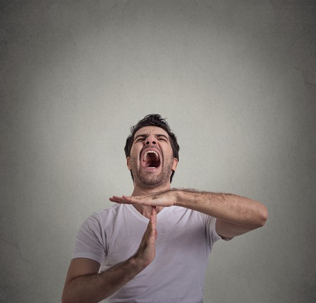 out time: Young man showing time out hand gesture, frustrated screaming to stop isolated on gray wall background. Too many things to do. Human emotions face expression reaction