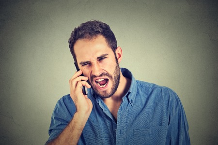 Closeup angry man, mad worker, pissed off employee shouting while on phone isolated on grey wall background. Negative human emotion face expression feeling attitude Stock Photo