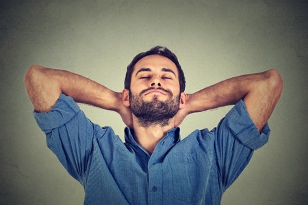 Closeup portrait of happy young man in blue shirt looking upwards in thought relaxing or napping isolated on gray wall background 免版税图像
