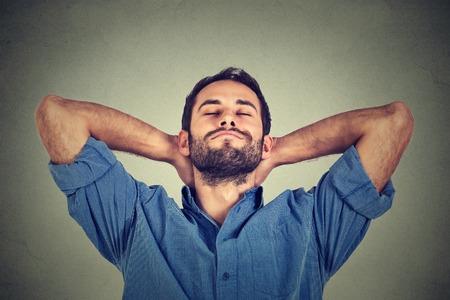 soñando: Primer retrato de hombre joven feliz en camisa azul mirando hacia arriba en el pensamiento de relajación o siestas aislado sobre fondo gris de la pared