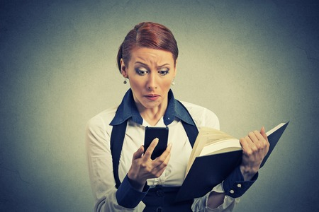 cell phone addiction: portrait upset young business woman looking at phone seeing bad news or photos holding book isolated on gray wall background. Human emotion reaction face expression. Complicated new technology concept
