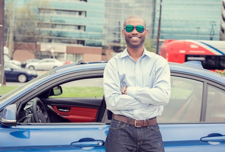 african american man: Happy man driver smiling standing by his new sport blue car isolated outside parking lot background. Handsome young man excited about his new vehicle. Positive face expression