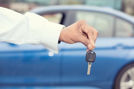 lot of: Male hand holding car keys offering new blue car on background