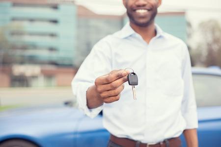 key: Happy smiling man holding car keys offering new blue car on background