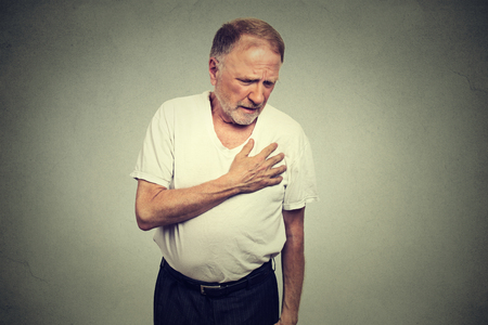 catastrophic: senior mature man suffering from bad pain in his chest heart attack isolated on gray background Stock Photo