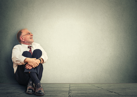 retirement happy man: Thinking senior man sitting on floor isolated on gray wall  background. Mature male model corporate executive  smiling looking up dreaming