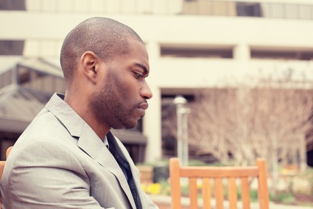 man sad: side profile portrait stressed young businessman sitting outside corporate office  looking down. Negative human emotion facial expression feelings.