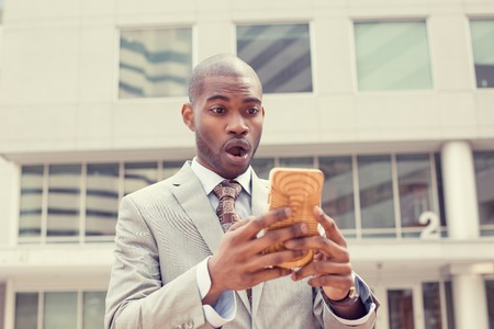 insulted: Closeup portrait anxious young business man looking at smart phone seeing bad news or photos with disgusting shocked face expression isolated outside city background. Human emotion, reaction Stock Photo