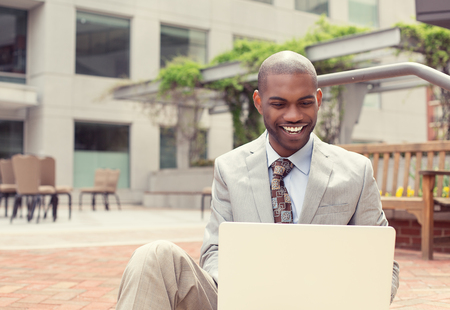 internet search: Handsome young happy businessman working on laptop computer outdoors on a background of corporate office building. Instagram filter effect
