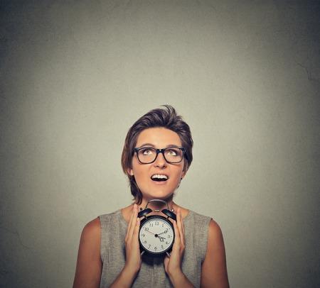 puntualidad: mujer sonriente joven con reloj despertador buscar aislado sobre fondo gris de la pared. Expresión de la cara humana. El tiempo, la puntualidad, la apretada agenda concepto