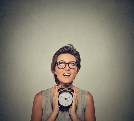 hurry up: young smiling woman with alarm clock looking up isolated on grey wall background. Human face expression. Time, punctuality, busy schedule concept Stock Photo