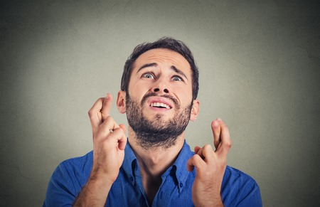 crossing fingers: Closeup portrait of young funny guy, business man crossing fingers, wishing, hoping for best, miracle isolated on gray background. Human emotions, facial expression feeling attitude