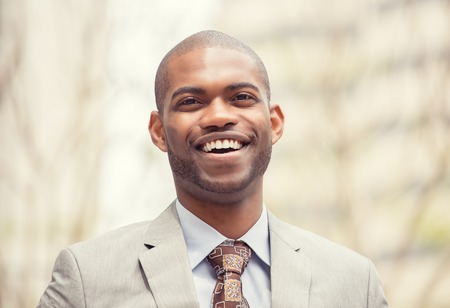 guy portrait: Headshot portrait of young professional man smiling laughing isolated on outside outdoors corporate office background. Positive human emotions feelings facial expressions Stock Photo