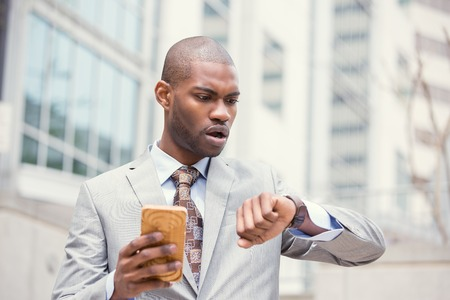 african american man: Business and time management concept. Stressed business man looking at wrist watch, running late for meeting standing outside corporate office. Worried face expression. Human emotion