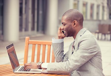 trabajo social: Perfil lateral apuesto hombre de negocios joven que trabaja con la computadora portátil al aire libre hablando por teléfono móvil. Efecto de filtro de Instagram. Hombre de negocios multitarea sentado en la mesa fuera de fondo de la oficina corporativa