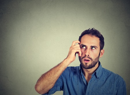 body expression: Closeup portrait young man scratching head, thinking deeply about something, looking up, isolated on grey wall background. Human facial expression, emotion, feeling, sign body language