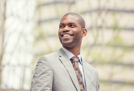 closeup portrait: Headshot portrait of young professional man smiling laughing isolated on outside outdoors corporate office background. Positive human emotions feelings facial expressions Stock Photo