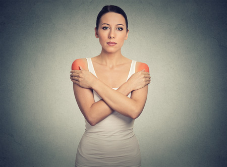 bilateral: Young woman with bilateral shoulder pain or stiffness colored in red isolated on gray wall background Stock Photo
