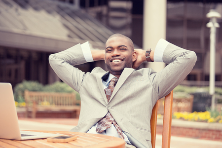 business casual: Portrait young happy businessman relaxing sitting at table outdoors corporate office background. Positive face expression