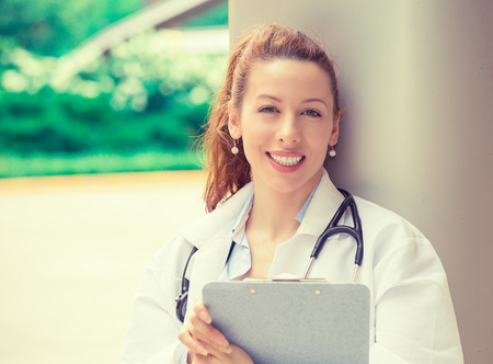 school nurse: Portrait confident happy young female doctor medical professional standing outside hospital clinic. Positive face expression Stock Photo
