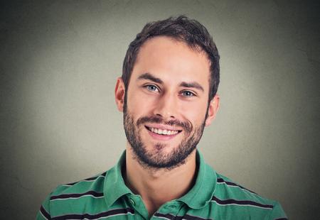 얼굴 만 웃는 현대 남자, 회색 벽 배경에 고립 된 창조적 인 전문가