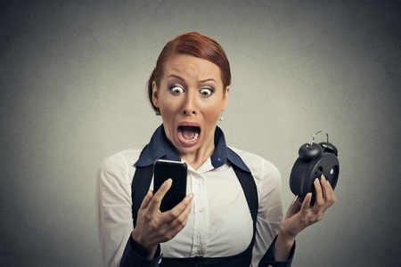 Portrait surprised business woman with alarm clock looking at smart phone with funny face expression late for meeting isolated on grey wall background. Human face expression emotions, feelings