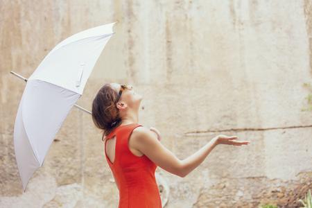 Schöne fröhliche junge Frau, die unter weißem Regenschirm