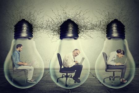 sedentario: Empleados Side empresa perfil sentadas en fila dentro de la bombilla de la lámpara eléctrica usando la computadora portátil aislada en el fondo gris de la pared de la oficina. Concepto de red de intercambio de ideas. Las condiciones de trabajo de la productividad Foto de archivo