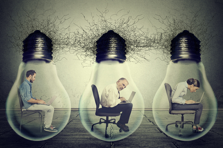 vision: Side profile company employees sitting in row inside electric lamp light bulb using laptop isolated on gray office wall background. Idea exchange network concept. Working conditions productivity