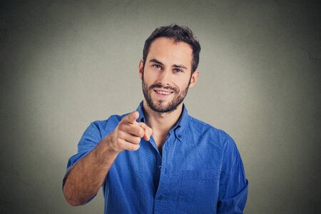 choose person: Handsome young man pointing finger at you isolated on gray wall background