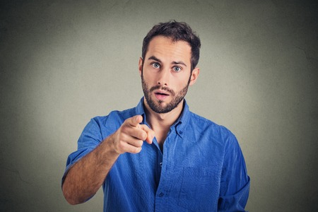 man pointing his finger at you camera gesture isolated on gray wall background Stock Photo