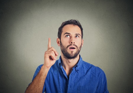 great idea: Portrait young man has an idea, pointing with finger up looking up isolated on grey wall background. Thoughtful guy solved a problem problem. Face expression,body language, life perception creativity