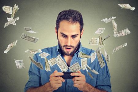 Technology online bankieren geld overmaken, concept van e-commerce. Geschokte jonge man met behulp van smartphone met dollarbiljetten vliegen weg van het scherm op een grijze muur kantoor achtergrond.
