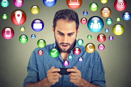 stunned: communication technology mobile phone high tech concept. Shocked handsome man using texting on smartphone application icons flying out of cellphone screen isolated on grey background. Face expression Stock Photo