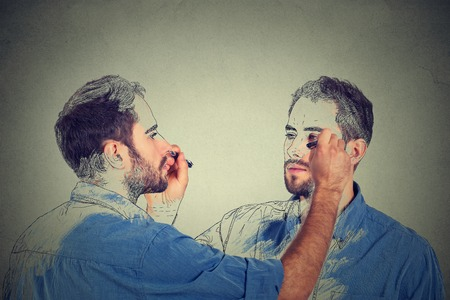 Skapa själv koncept. Bra ser ung man rita en bild, skiss av sig själv på grå vägg bakgrund. Mänskligt ansikte uttryck, kreativitet
