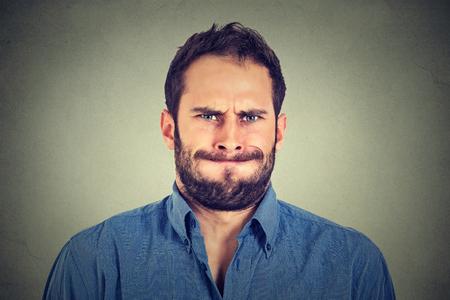 nerveux: Portrait Gros plan de jeune homme en col�re � propos d'avoir d�pression nerveuse isol� sur fond gris mur. Les �motions humaines les sentiments n�gatifs de l'expression faciale r�action d'attitude Banque d'images