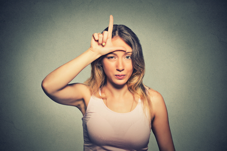 losers: Closeup portrait young unhappy woman giving loser sign on forehead, looking at you, disgust on face isolated on gray wall background. Negative human emotion facial expression Stock Photo