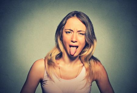 lengua afuera: Mujer divertida que muestra su lengüeta aislada en el fondo de la pared gris