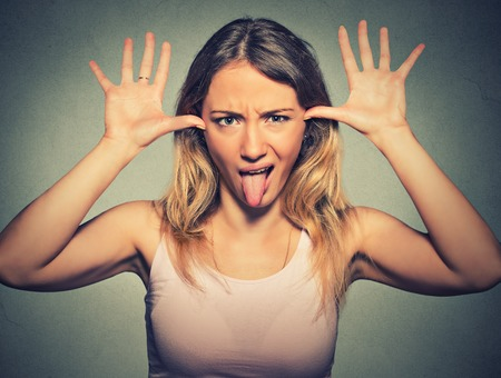 Young pretty woman with funny face mocking someone sticking her tongue out isolated on gray wall background