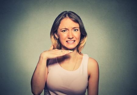 jovenes estudiantes: Mujer joven enojado haciendo un gesto con la mano para dejar de hablar, lo cortó a cabo, o que ella se llevará a su cabeza, aislado sobre fondo gris. La emoción negativa, las expresiones faciales, los sentimientos