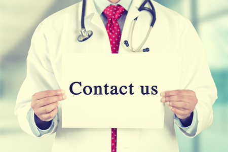 care providers: Closeup doctor hands holding white card sign with contact us text message isolated on hospital clinic office background.