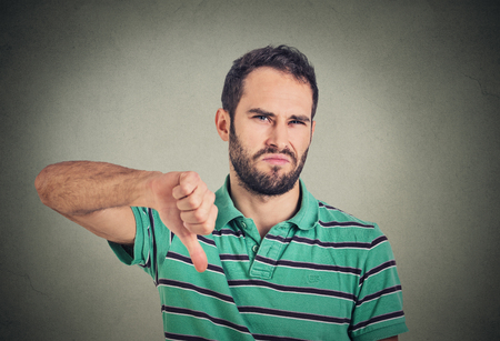 handsome men: Closeup portrait angry, unhappy, young man showing thumbs down sign, in disapproval of offer situation isolated on gray background. Negative human emotions, facial feelings Stock Photo